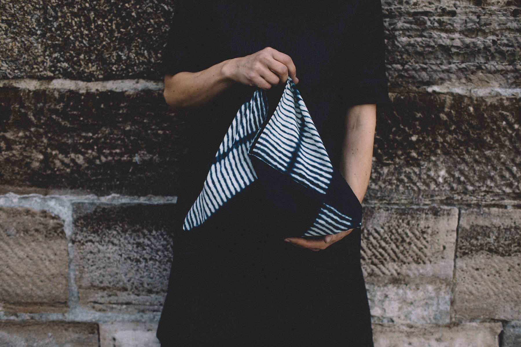 Model holding a cloth bag with shibori design