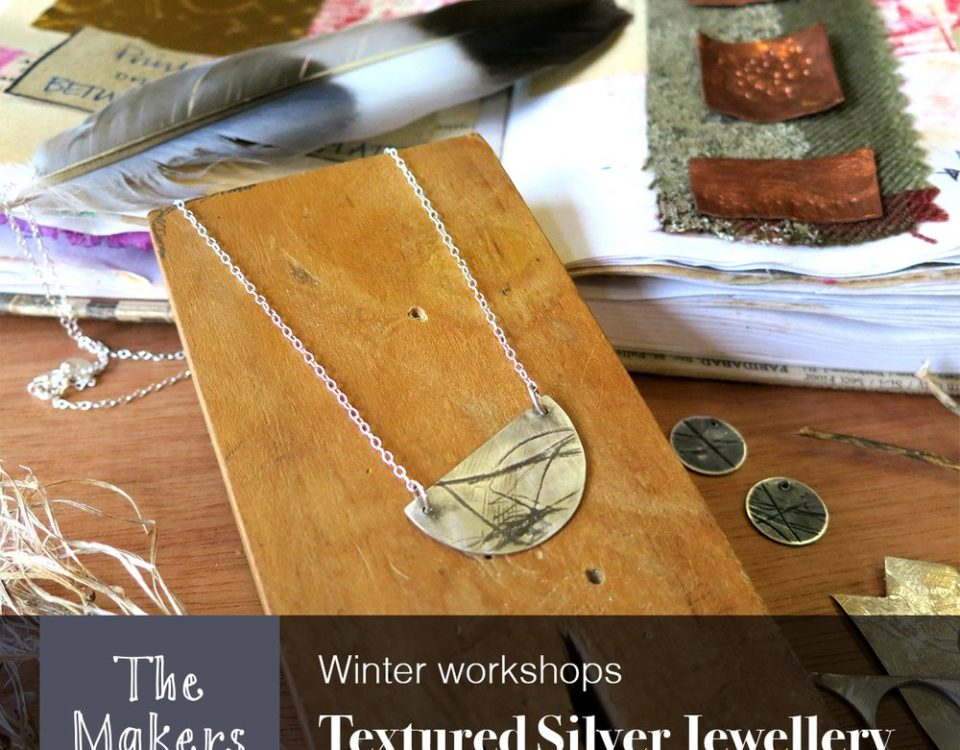 Silver jewellery necklace displayed on wooden block